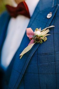 Il budier dello sposo di fiori gialli su una giacca a scacchi e un papillon rosso