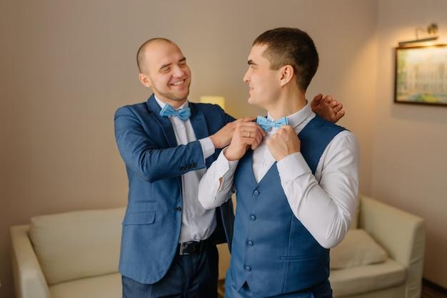 Groomsmen in vestito blu che aiuta sposo felice che si prepara al mattino per cerimonia di nozze. uomo di lusso in tuta in camera. giorno del matrimonio.