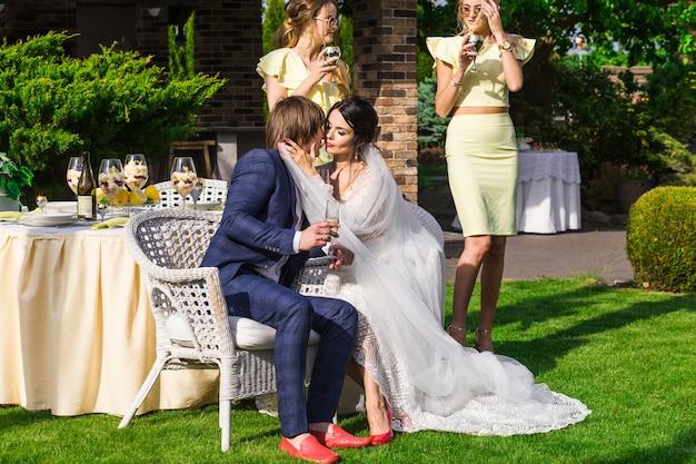 Groomsmen e damigelle con sposi novelli alla cerimonia di nozze