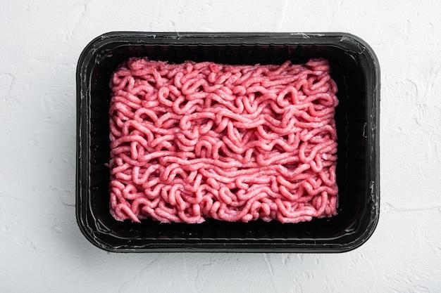 Carne di manzo macinata in vassoio di plastica, su pietra bianca