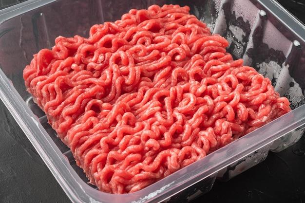 Carne macinata in vassoio di plastica con carne macinata cruda fatta in casa, su sfondo di pietra nera