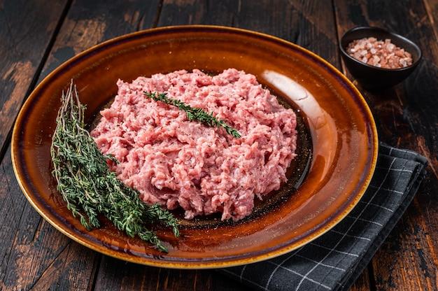 Pollo macinato o carne di tacchino, pollame crudo su piatto rustico con erbe aromatiche. sfondo scuro. vista dall'alto.