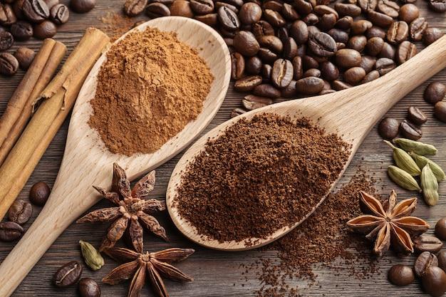 Caffè macinato e cannella in cucchiaio accanto ai chicchi di caffè