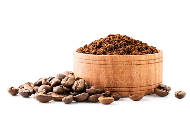 Caffè macinato in un piatto di legno e chicchi di caffè isolati.