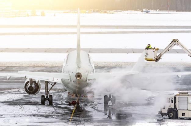 Il personale di terra fornisce lo sbrinamento. stanno spruzzando l'aereo, il che impedisce il verificarsi di gelate.