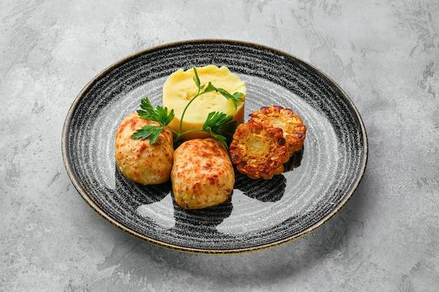 Cotoletta di carne macinata con purè di patate e fette di mais grigliate