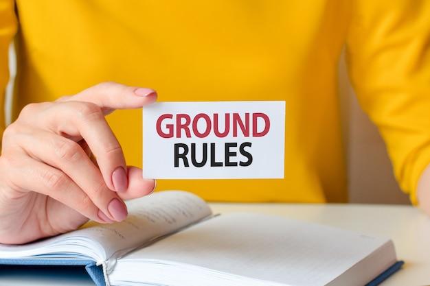 Le regole di base sono scritte su un biglietto da visita bianco. la mano di una donna tiene una carta di carta bianca.