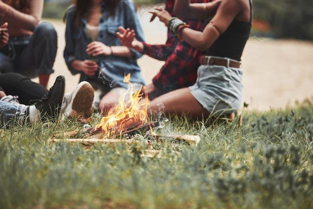 Vista a terra. un gruppo di persone fa un picnic sulla spiaggia. gli amici si divertono durante il fine settimana.