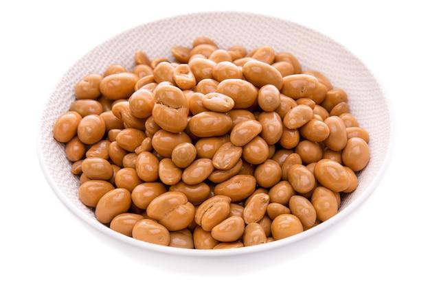 L'arachide in glassa al caramello in un piatto bianco su uno sfondo bianco ha isolato oggetti e prodotti