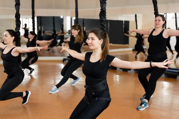 Un gruppo di ragazze sportive attive in abiti sportivi neri sono impegnati nella forma fisica del budgie in palestra