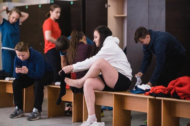 Gruppo di giovani donne attive che si siedono sulla panchina in spogliatoio e vestirsi per l'allenamento sportivo