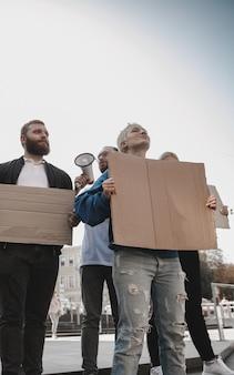 Gruppo di attivisti che danno slogan in un raduno uomini e donne che marciano insieme in una protesta nel
