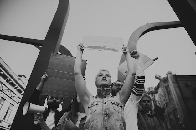 Gruppo di attivisti che danno slogan in una manifestazione uomini e donne che marciano insieme in una protesta