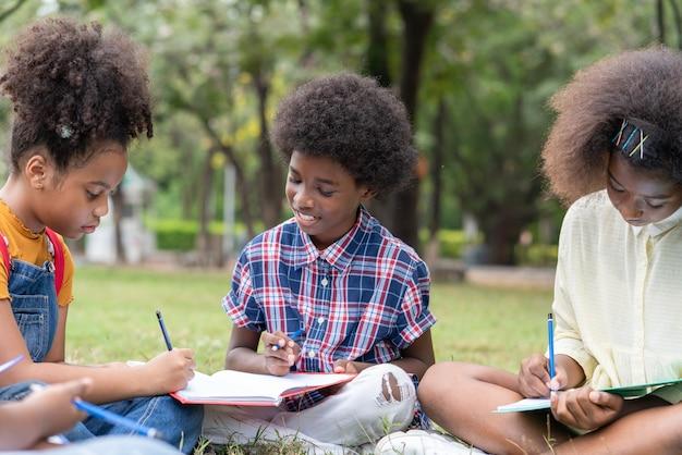Gruppo di bambini afroamericani o bambini afro seduti sul prato che si divertono a usare le matite disegnando sui libri con gli amici fuori dalle aule nel parco della scuola educazione all'aperto