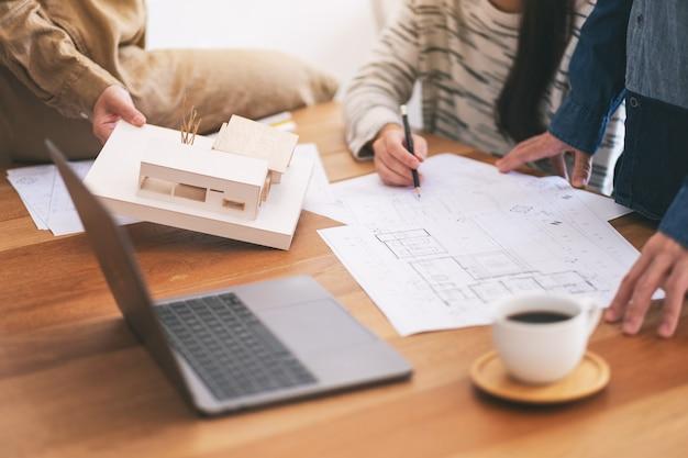 Gruppo di un architetto che tiene e discute di un modello di architettura con carta da disegno per negozio sul tavolo in ufficio
