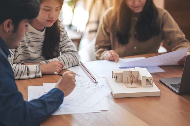 Gruppo di un architetto che lavora e discute su un modello di architettura insieme alla carta da disegno del negozio sul tavolo in ufficio
