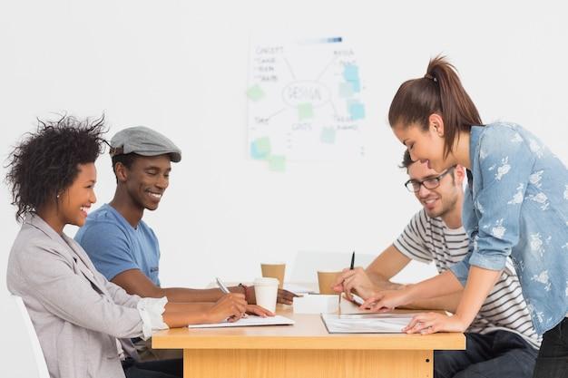 Gruppo di artisti in discussione allo scrittorio all'ufficio