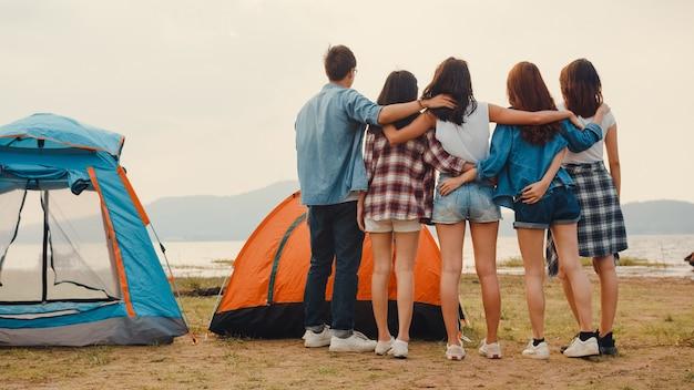 Il gruppo di adolescenti asiatici migliori amici si divertono a guardare una bella vista del tramonto e godersi momenti felici insieme accanto al campo e alle tende nel parco nazionale