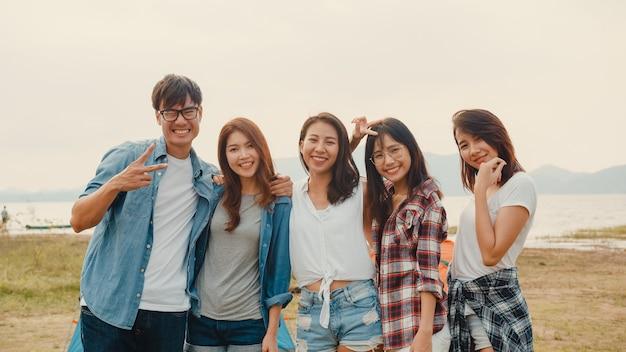 Un gruppo di adolescenti asiatici migliori amici scattano foto con la fotocamera automatica e si godono momenti felici insieme accanto al campo e alle tende nel parco nazionale