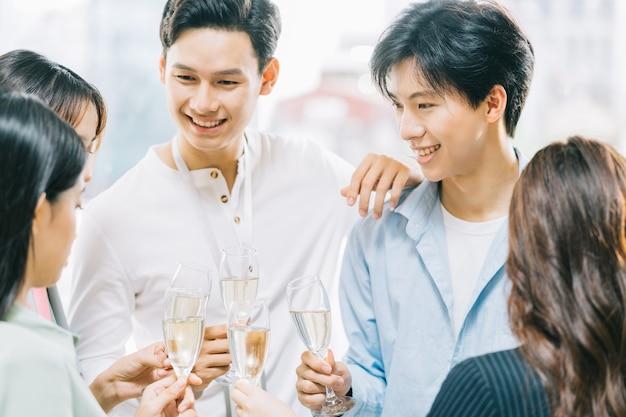 Gli uomini d'affari asiatici del gruppo stanno facendo un brindisi insieme e chiacchierando a una festa aziendale