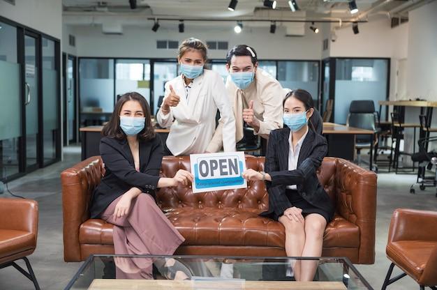 Un gruppo di uomini d'affari asiatici che indossa la maschera per il viso seduto e tenendo riaprire e mantenere la carta di allontanamento sociale in ufficio moderno