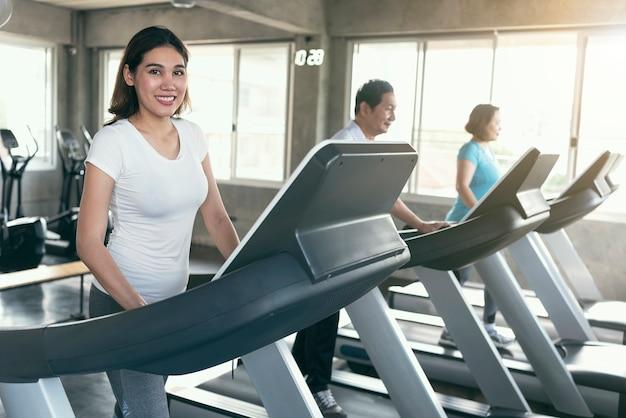 Raggruppi il corridore asiatico di esercizio della famiglia a forma fisica della palestra che sorride e felice. uno stile di vita sano.