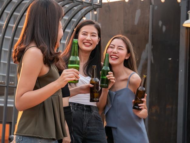 Gruppo di amici asiatici tifo e bere alla festa in terrazza. giovani che godono e che vanno in giro sul tetto al tramonto