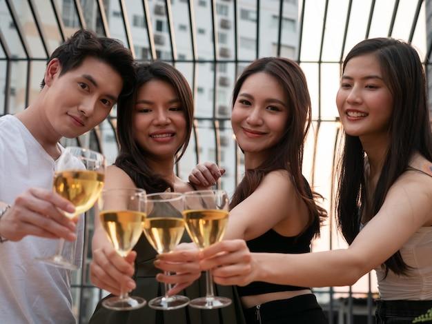 Gruppo di amici asiatici tifo e bere alla festa in terrazza. giovani che tostano vetro con vino al ristorante sul tetto