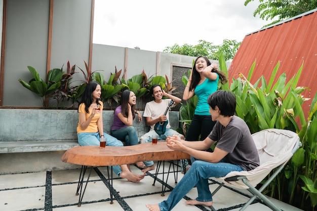 Gruppo di amici asiatici divertendosi cantando e suonando la chitarra insieme nel cortile di casa