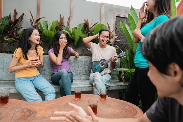 Gruppo di amici asiatici divertendosi mentre si mangia e si beve nel cortile di casa