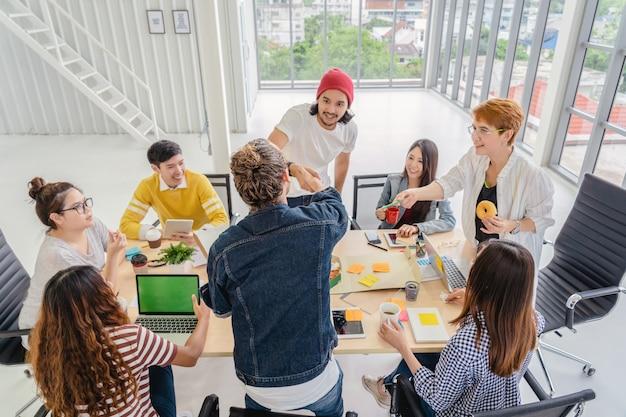 Gruppo di uomini d'affari asiatici e multietnici di brainstorming e handshaking mentre eatting