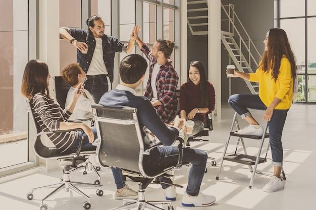 Gruppo di uomini d'affari asiatici e multietnici con abiti casual che parlano e fanno brainstorming