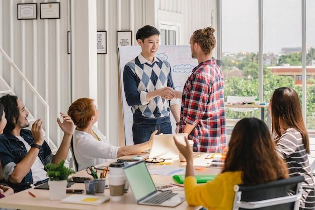 Il gruppo di gente di affari asiatica e multietnica con il vestito casuale accoglie favorevolmente la nuova squadra del membro