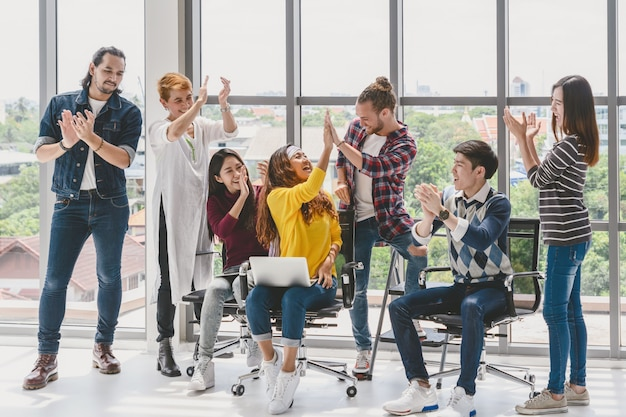 Gruppo di gente di affari asiatica e multietnica con il vestito casuale che lavora con l'azione felice