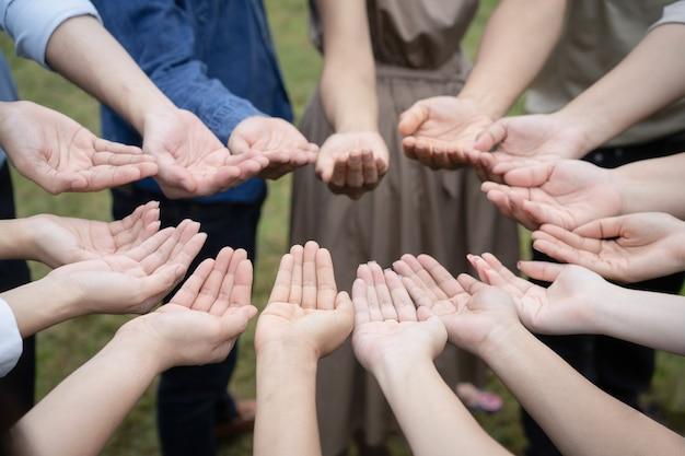 Un gruppo di persone asiatiche alza la mano destra e maneggia delicatamente per ottenere e condividere buoni sentimenti insieme nel training teambuilding.