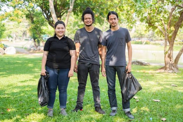 Gruppo di giovani volontari asiatici che raccolgono rifiuti in parco. concetto di protezione ambientale