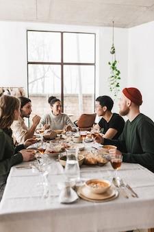 Gruppo di amici internazionali attraenti seduti al tavolo pieno di cibo che parlano sognante insieme
