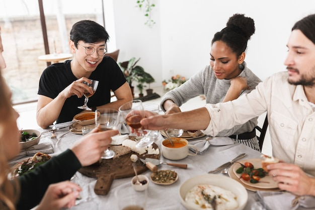 Gruppo di amici internazionali attraenti seduti al tavolo pieno di cibo che trascorrono felicemente del tempo insieme