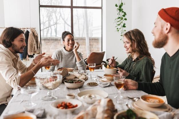Gruppo di amici internazionali attraenti seduti al tavolo pieno di cibo che parlano felicemente tra loro