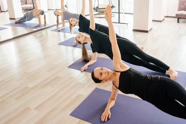 Gruppo di ragazze attraenti di sport in abiti sportivi che lavorano nella sala fitness.