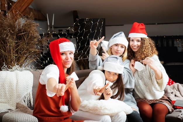 Un gruppo di amici di ragazze donne attraenti in cappelli di babbo natale e maschere per il viso prende un autoritratto di vacanza