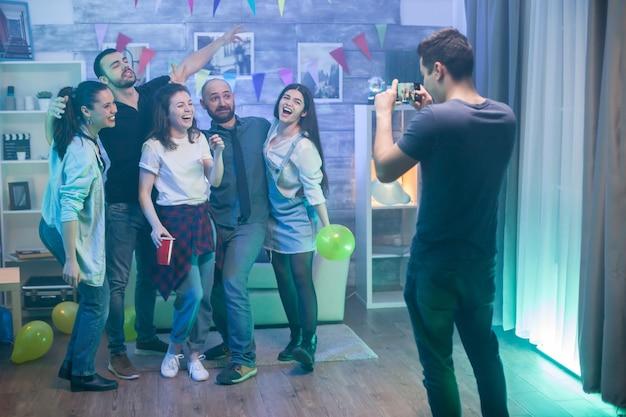 Gruppo di uomini belli e attraenti che guardano il loro amico mentre scattano una foto.