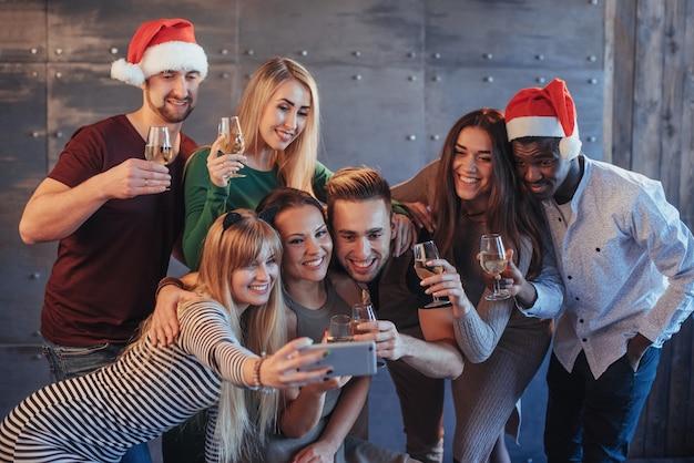 Raggruppa i bei giovani che fanno selfie nella festa di capodanno, le ragazze e i ragazzi dei migliori amici che si divertono insieme, posando le persone di stile di vita emotivo. cappelli di babbo natale e bicchieri di champagne nelle loro mani