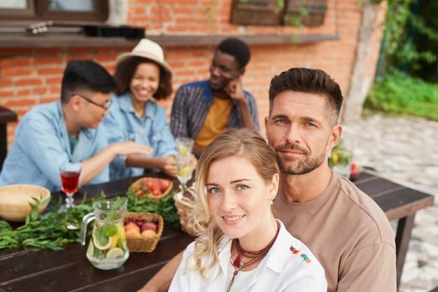 Gruppo di bei giovani che godono della cena all'aperto alla luce del sole, concentrarsi sulla coppia sorridente in primo piano