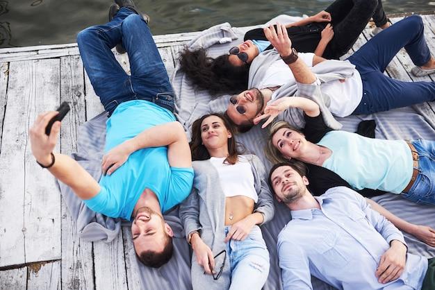 Gruppo di bei giovani che fanno selfie sdraiato sul molo