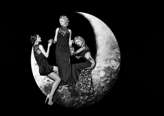 Gruppo di belle giovani donne in posa sulla falce di luna in abito elegante da sera lungo