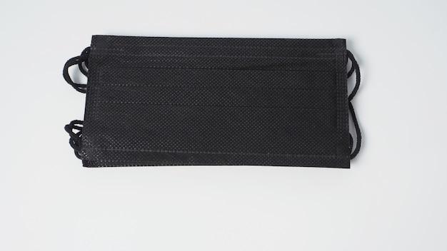 Gruppo di maschera facciale monouso nera su sfondo bianco.