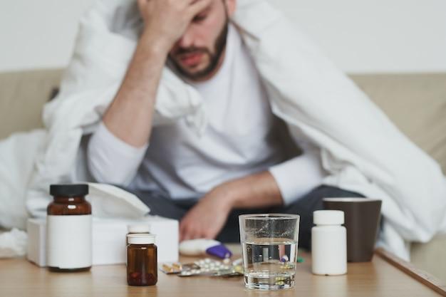Gruppo di bottiglie con pillole e bicchiere d'acqua sul tavolo e giovane malato avvolto in una coperta che tocca la sua testa mentre era seduto sul letto