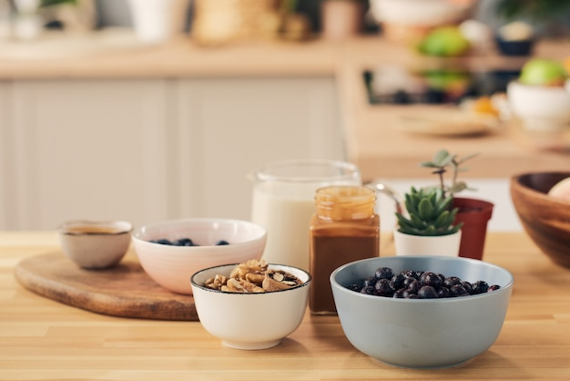 Gruppo di ciotole e vasetti con ingredienti per frullato