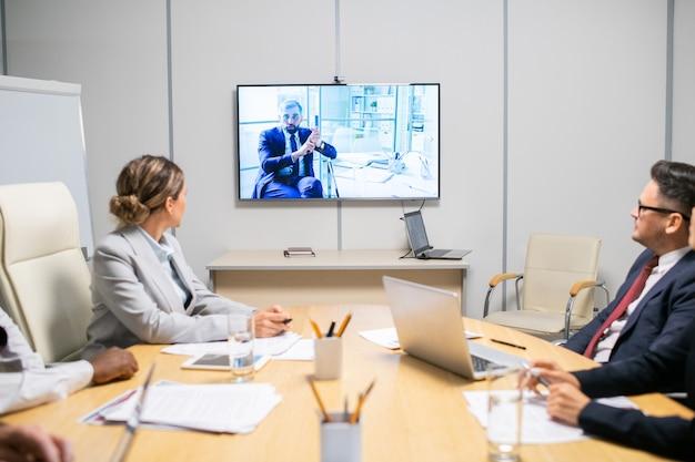 Gruppo di broker che ascoltano un uomo d'affari maturo su un grande display